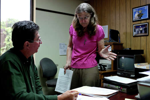 Joleen Cahill wraps up loose ends with Investigator Douglas C. Knukel on what was supposed to be her final day of work as a legal secretary with the Milam County District Attorneys office in Cameron on Tuesday, July 16, 2013. Photo: Lisa Krantz, San Antonio Express-News / San Antonio Express-News