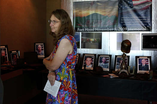 Joleen Cahill stands by the display of bronze sculptures by sculptor Troy Kelly memorializing the 13 victims for the Ft. Hood November 5, 2009 Memorial that Cahill and others are working to have built, after a meeting of the memorial's committee at the Killeen Convention Center on July 2, 2013. Photo: Lisa Krantz, San Antonio Express-News / San Antonio Express-News