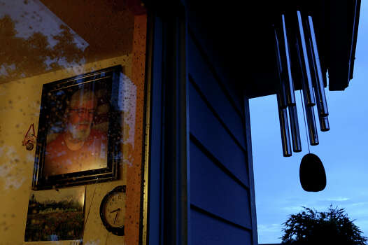 Wind chimes holding ashes of Mike Cahill, in the photograph at left, hang outside the home he shared with his wife, Joleen Cahill, where she still lives in Cameron on Tuesday, July 16, 2013. Photo: Lisa Krantz, San Antonio Express-News / San Antonio Express-News