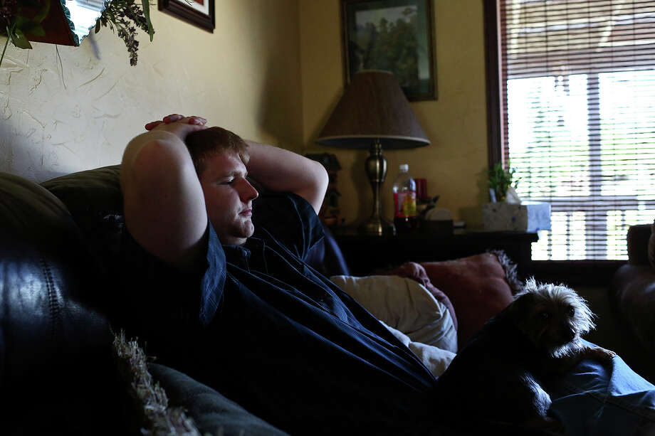 """George Stratton III, 22, relaxes with his dog, Scooter, at his family's home in Post Falls, ID, on Thursday, July 25, 2013.  """"He's my best friend,"""" Stratton says of his dog. Photo: Lisa Krantz, San Antonio Express-News / San Antonio Express-News"""