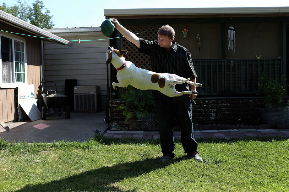 George Stratton III, 22, plays with Kia, one of four dogs in his family, at home in Post Falls, ID, on Friday, July 26, 2013. Photo: Lisa Krantz, San Antonio Express-News / San Antonio Express-News