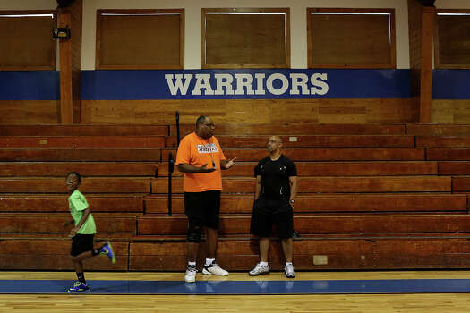 Alonzo Lunsford, left, talks with Nelson Morris, a parent of a participant in Lunsford's summer basketball camp, while Amare Bethel, 8, runs by during the Saturday morning workout at Fayetteville Christian School in Fayetteville, NC, on Saturday, July 20, 2013. Lunsford is the school's associate head coach for women's basketball and the head coach for junior varsity. Photo: Lisa Krantz, San Antonio Express-News / San Antonio Express-News