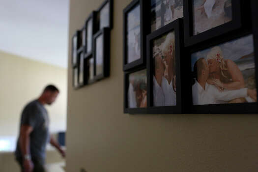 Wedding pictures taken in Hawaii one month before Shawn Manning was shot at Ft. Hood decorate a wall in the home he shares with his wife, Autumn. Photo: Lisa Krantz, San Antonio Express-News / San Antonio Express-News