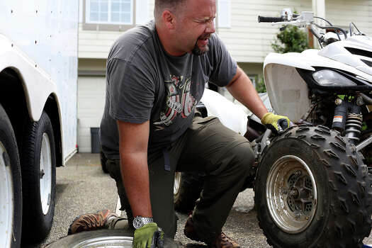 Shawn Manning winces as he struggles to get up from changing tires on an ATV Raptor for a camping trip with friends outside his home in Lacey, WA on Sunday, July 7, 2013. Photo: Lisa Krantz, San Antonio Express-News / San Antonio Express-News