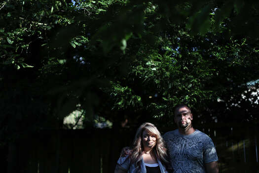 Shawn Manning stands with his wife, Autumn, in their backyard, where they spend much of their free time barbecuing, gardening and playing with their pugs. Autumn quickly learned what it was to be a military wife when Shawn was shot six times one month into their marriage. Photo: Lisa Krantz, San Antonio Express-News / San Antonio Express-News