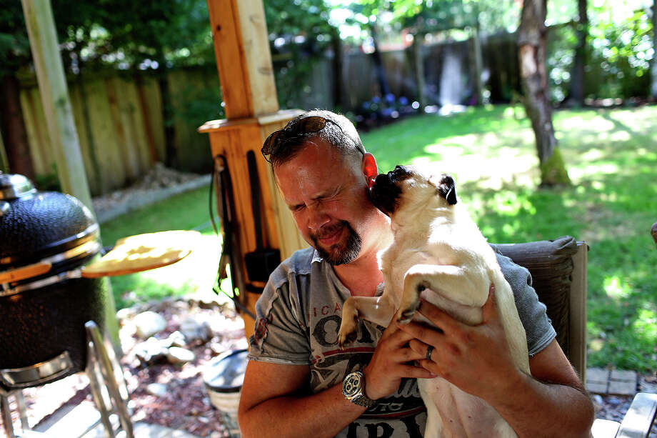 Shawn Manning gets kisses from Cleo, one of his two pugs, at his home in Lacey, WA on Saturday, July 6, 2013. Photo: Lisa Krantz, San Antonio Express-News / San Antonio Express-News