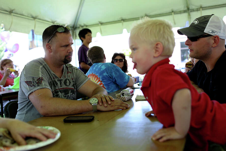 Shawn Manning, left, hangs out with his best friend, Army Reserve Staff Sgt. Todd Ayres, right, with Ayres son, Jake,  during a BBQ festival in Lacey, WA. Manning was texting his wife and Ayres, who was also on Ft. Hood but not at the SRP, as the shooting began. Photo: Lisa Krantz, San Antonio Express-News / San Antonio Express-News