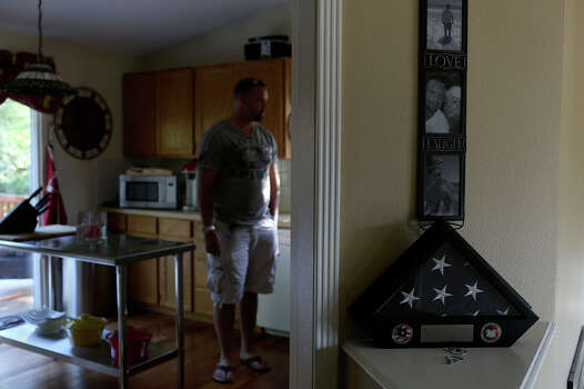 Shawn Manning stands in his kitchen, near a flag he received as an award after a deployment to Iraq, at his home in Lacey, WA. Manning was preparing for his third deployment, this time to Afghanistan, when he was shot at Ft. Hood. Photo: Lisa Krantz, San Antonio Express-News / San Antonio Express-News