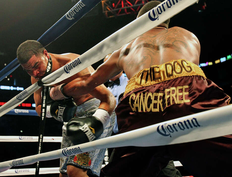 Anthony Hanshaw (left) gets tangled in the ropes as Anthony Dirrell moves in for the TKO during the Knockout Kings II boxing card at the AT&T Center on July 27, 2013. Photo: TOM REEL, San Antonio Express-News
