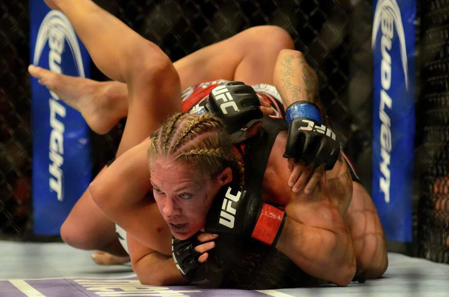 Julie Kedzie has her opponent, Germaine de Randamie in a headlock during their Bantamweight fight Saturday, July 27, 2013, at the KeyArena in Seattle. Randamie won the fight. Photo: SY BEAN, SEATTLEPI.COM / SEATTLEPI.COM