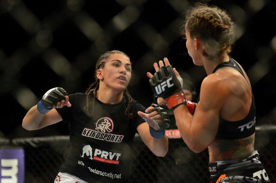 Jessica Andrade throws a punch at her opponent Liz Carmouche during their Bantamweight fight Saturday, July 27, 2013, at the KeyArena in Seattle. Andrade lost the fight. Photo: SY BEAN, SEATTLEPI.COM / SEATTLEPI.COM