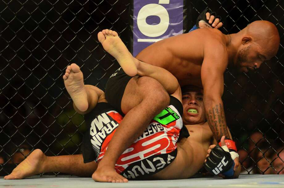 Demetrious Johnson of Parkland, Washington, wrestles his opponent, John Moraga of Phoenix, Arizona, to the ground Saturday, July 27, 2013, at the KeyArena in Seattle. Johnson won the fight, keeping his Championship title. Photo: SY BEAN, SEATTLEPI.COM / SEATTLEPI.COM