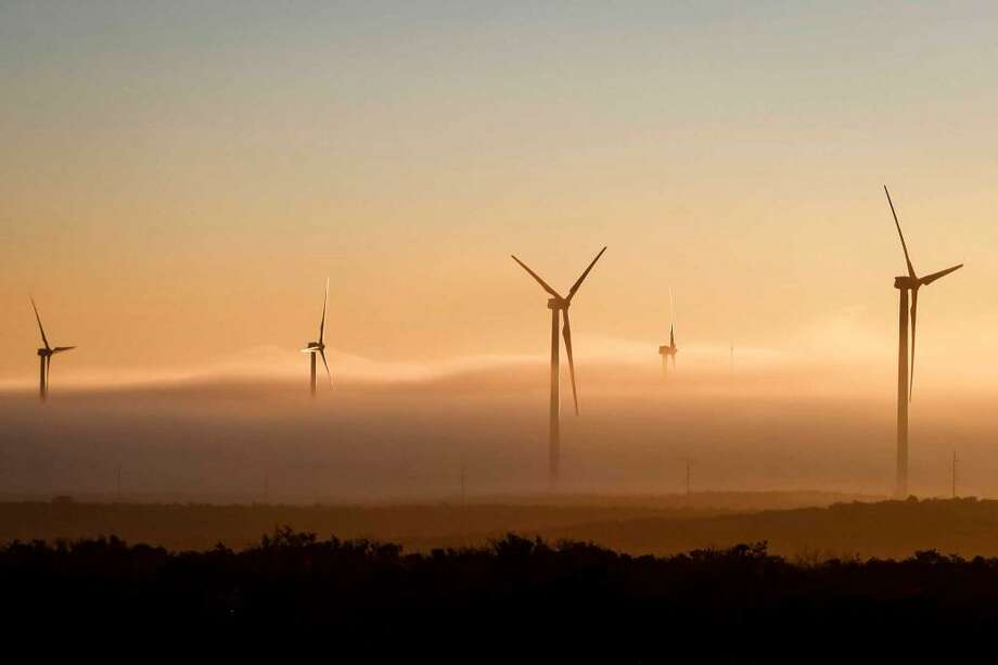 A thick cloud of fog and morning light engulfs several 285ft tall 2.5 MW Clipper wind turbines at the BP Sherbino Mesa II Wind Farm. BP announced in April that it is leaving the wind business. Photo: Michael Paulsen, Houston Chronicle