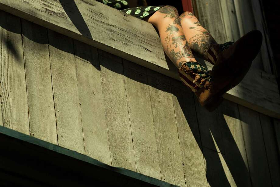 Tattooed legs and American flag boots dangle from a window overlooking the second day of Capitol Hill Block Party Saturday, July 27, 2013, in the Capitol Hill neighborhood of Seattle. The festival continues Sunday. Photo: JORDAN STEAD, SEATTLEPI.COM / SEATTLEPI.COM