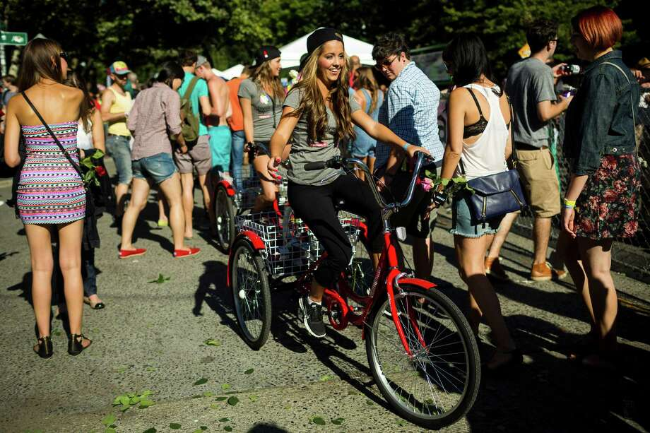 A Vitamin Water representative rides around the festival, giving out free drinks on the second day of Capitol Hill Block Party Saturday, July 27, 2013, in the Capitol Hill neighborhood of Seattle. The festival continues Sunday. Photo: JORDAN STEAD, SEATTLEPI.COM / SEATTLEPI.COM