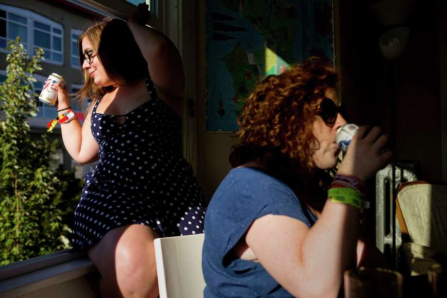 Lindsey Bluher, left, and Keegan Prosser, right, enjoy beers from a high-rise loft on the second day of Capitol Hill Block Party Saturday, July 27, 2013, in the Capitol Hill neighborhood of Seattle. The festival continues Sunday. Photo: JORDAN STEAD, SEATTLEPI.COM / SEATTLEPI.COM