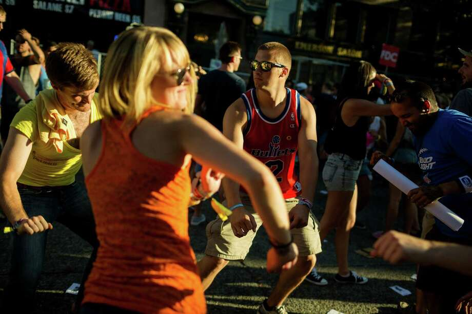 Fans dance in the golden light of East Pike Street during the second day of Capitol Hill Block Party Saturday, July 27, 2013, in the Capitol Hill neighborhood of Seattle. The festival continues Sunday. Photo: JORDAN STEAD, SEATTLEPI.COM / SEATTLEPI.COM