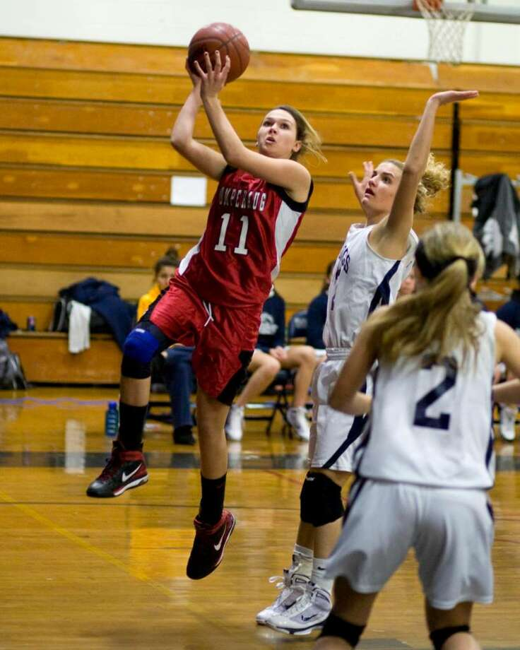 Pomperaug's Haili Welton (11) drives around Immaculate defender Jen Daily during their SWC game Tuesday night at Immaculate High. Photo: Barry Horn / The News-Times Freelance