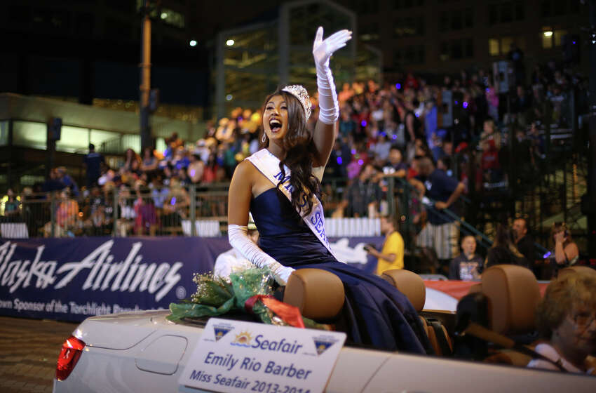 Newly crowned Miss Seafair, Emily Rio Barber, waves from her car during the annual Seafair Torchlight Parade on Saturday, July 27, 2013 in downtown Seattle. Fourth Avenue was lined with thousands of people during the parade that featured 106 entries.