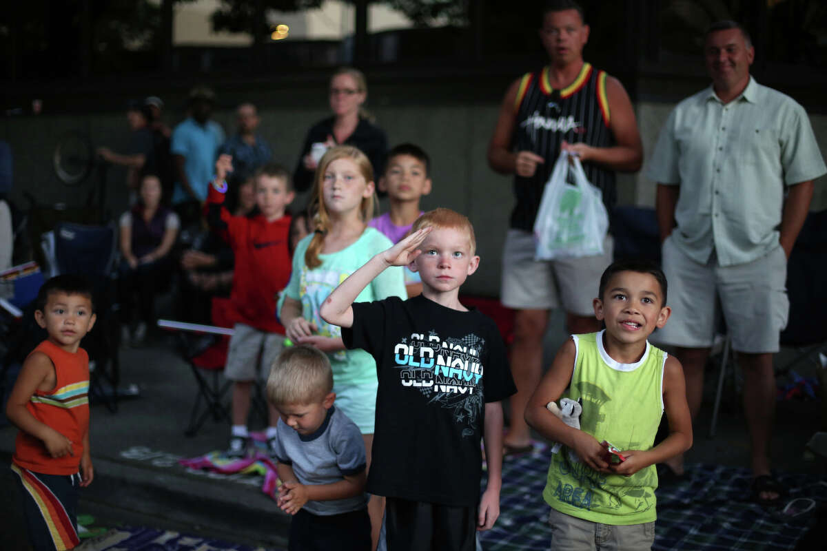 A young spectator salutes as members of the U.S. Army pass during the annual Seafair Torchlight Parade on Saturday, July 27, 2013 in downtown Seattle. Fourth Avenue was lined with thousands of people during the parade that featured 106 entries.