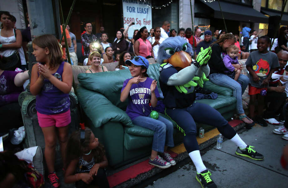 Spectators react to Seahawks mascot Blitz grabbing a seat on their couch during the annual Seafair Torchlight Parade on Saturday, July 27, 2013 in downtown Seattle. Fourth Avenue was lined with thousands of people during the parade that featured 106 entries. Photo: JOSHUA TRUJILLO, SEATTLEPI.COM / SEATTLEPI.COM