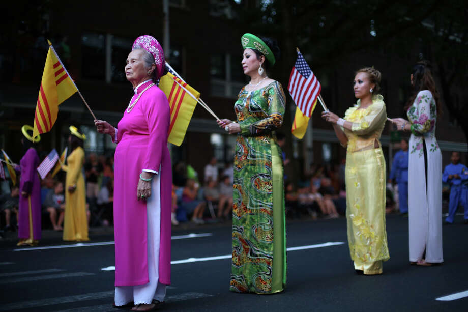 Members of the Vietnamese community hold flags during the annual Seafair Torchlight Parade on Saturday, July 27, 2013 in downtown Seattle. Fourth Avenue was lined with thousands of people during the parade that featured 106 entries. Photo: JOSHUA TRUJILLO, SEATTLEPI.COM / SEATTLEPI.COM