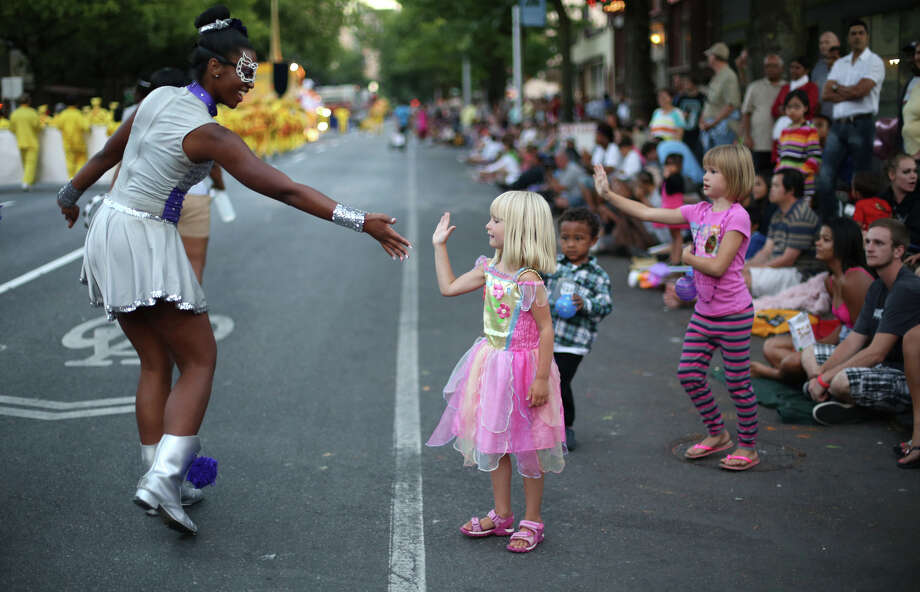 A parade spectator gets a high-five from a member of a drill team during the annual Seafair Torchlight Parade on Saturday, July 27, 2013 in downtown Seattle. Fourth Avenue was lined with thousands of people during the parade that featured 106 entries. Photo: JOSHUA TRUJILLO, SEATTLEPI.COM / SEATTLEPI.COM