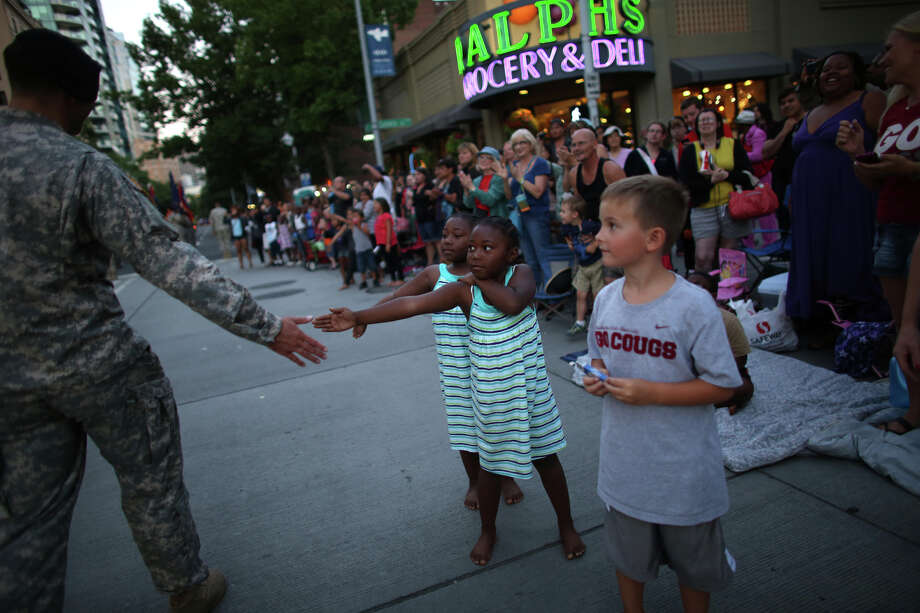 Young girls greet a solider during the annual Seafair Torchlight Parade on Saturday, July 27, 2013 in downtown Seattle. Fourth Avenue was lined with thousands of people during the parade that featured 106 entries. Photo: JOSHUA TRUJILLO, SEATTLEPI.COM / SEATTLEPI.COM