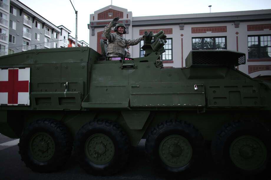 A solider waves from a Stryker vehicle during the annual Seafair Torchlight Parade on Saturday, July 27, 2013 in downtown Seattle. Fourth Avenue was lined with thousands of people during the parade that featured 106 entries. Photo: JOSHUA TRUJILLO, SEATTLEPI.COM / SEATTLEPI.COM
