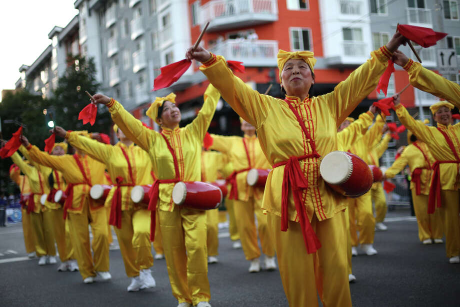 Members of the Falun Dafa entry perform during the annual Seafair Torchlight Parade on Saturday, July 27, 2013 in downtown Seattle. Fourth Avenue was lined with thousands of people during the parade that featured 106 entries. Photo: JOSHUA TRUJILLO, SEATTLEPI.COM / SEATTLEPI.COM