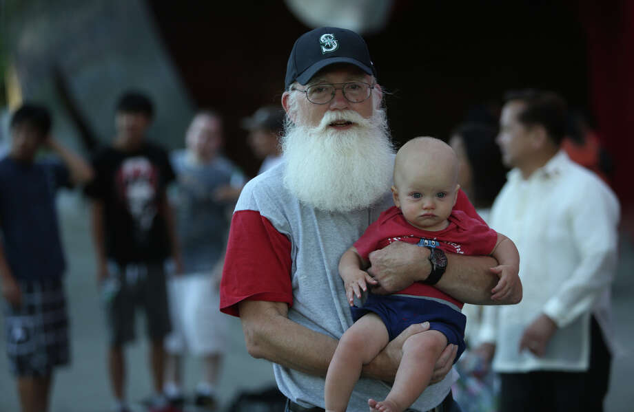 Mark Johnson and his grandson Micha look at the floats during the annual Seafair Torchlight Parade on Saturday, July 27, 2013 in downtown Seattle. Fourth Avenue was lined with thousands of people during the parade that featured 106 entries. Photo: JOSHUA TRUJILLO, SEATTLEPI.COM / SEATTLEPI.COM