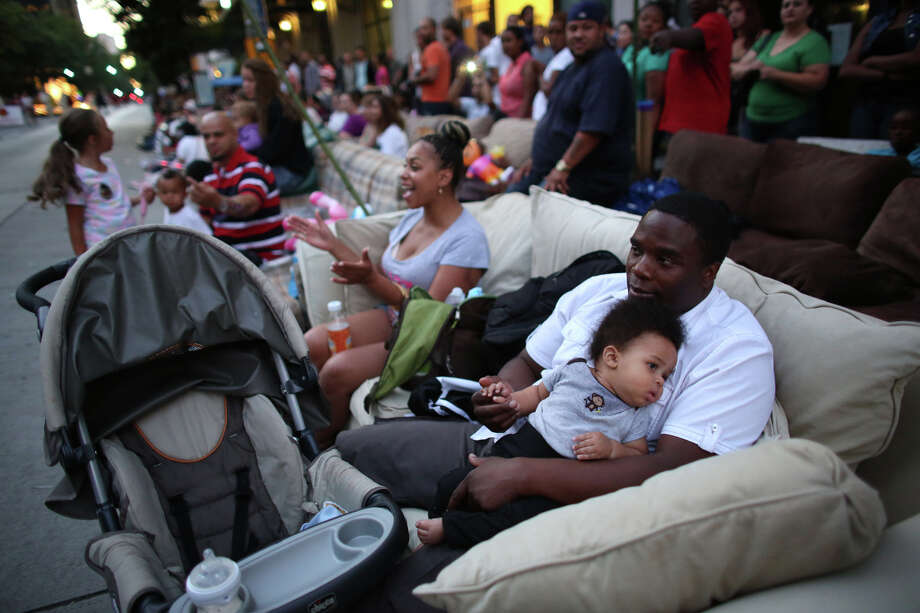 LaMar Thomas and his son Kaleb watch the entries during the annual Seafair Torchlight Parade on Saturday, July 27, 2013 in downtown Seattle. Fourth Avenue was lined with thousands of people during the parade that featured 106 entries. Photo: JOSHUA TRUJILLO, SEATTLEPI.COM / SEATTLEPI.COM