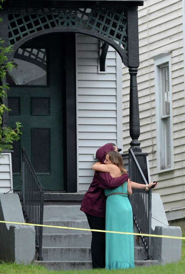 Two people hug near the fire scene at 102-108 Woodlawn Avenue July 28, 2013 in Saratoga Springs, N.Y.  15 people were left homeless and four structures were heavily damaged. (Skip Dickstein/Times Union) Photo: SKIP DICKSTEIN