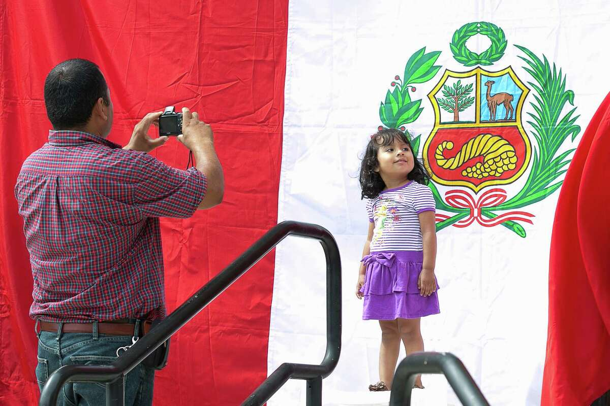 Victor Trejo of Stamford snaps a photo of his 3 year old daughter Amy in front of the Peruvian Flag during Sunday's afternoon South American country's independence day celebration day event at Old Town Hall.