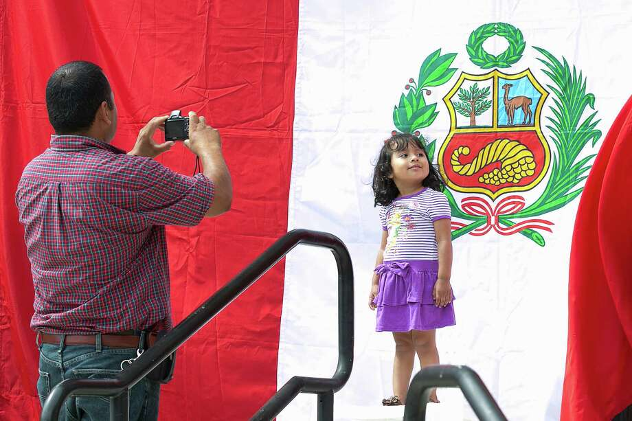 Victor Trejo of Stamford snaps a photo of his 3 year old daughter Amy in front of the Peruvian Flag during Sunday's afternoon South American country's independence day celebration day event at Old Town Hall. Photo: Mike Ross / Mike Ross Connecticut Post freelance - @www.mikerossphoto.com
