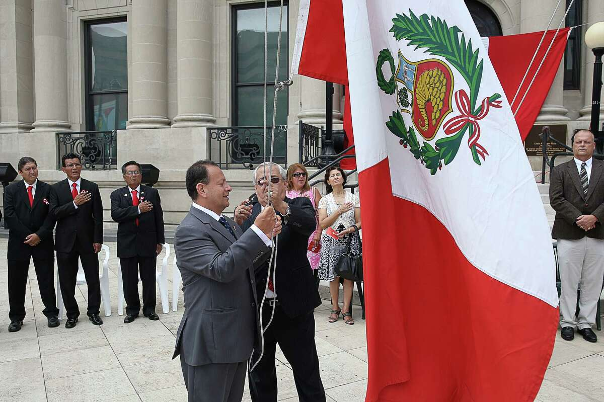 Deputy Consul of Peru Julio Cadenillas, left and Peruvian American Community Center of Connecticut board member Willy Giraldo raise the Peruvian Flag during Sunday's afternoon South American country's independence day celebration day event at Old Town Hall.