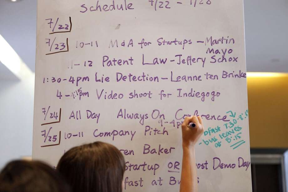 Andrea Draper, Program Director at Draper University, a boarding school for wanna-be entrepreneurs, updates the weekly schedule for the following morning on the dry erase board walls at Draper University in San Mateo, Calif. on July 23, 2013. Photo: Katie Meek, The Chronicle