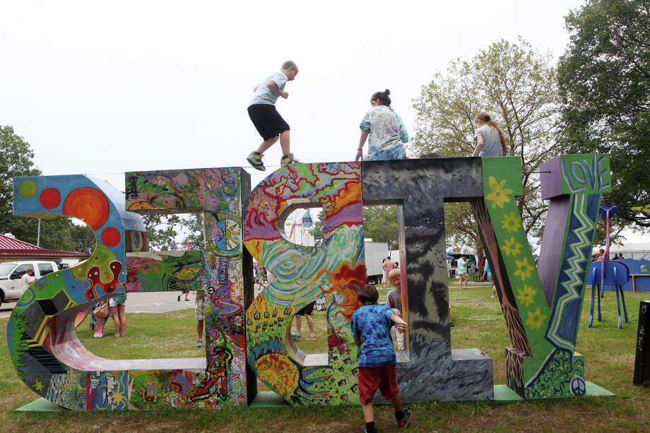 Children play on the VIBES sign at the 18th annual Gathering of the Vibes Musical Festival at Seaside Park in Bridgeport, Conn. on Sunday, July 28, 2013. Photo: BK Angeletti, B.K. Angeletti / Connecticut Post freelance B.K. Angeletti