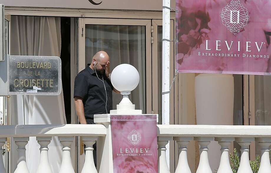 A police officer stands outside the Carlton InterContinental Hotel, which is hosting a show by the Leviev diamond house. A thief made off with an estimated $50 million worth of jewels. Photo: Lionel Cironneau, Associated Press