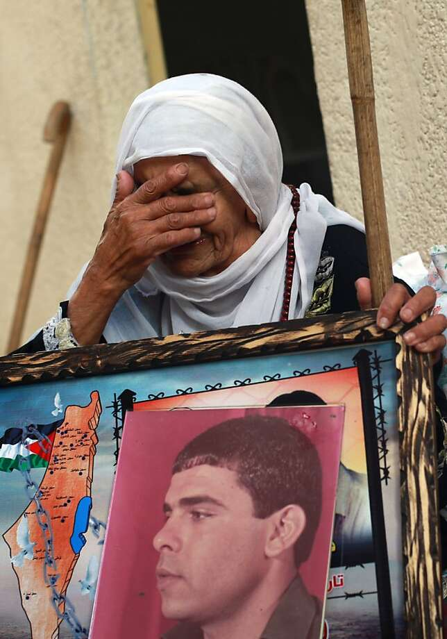 Mother of Palestinian Fares Baroud, who has been held in an Israeli prison for 22 years, cries as she holds his picture after hearing news on the possible release of her son at her house in Shati refugee camp in Gaza City on July 28, 2013. Baroud is expected to be among the 104 Arab prisoners to be released by Israeli authorities in a step to renew stalled peace talks with the Palestinians. The 22-member cabinet approved Prime Minister Benjamin Netanyahu's proposal to free prisoners by a vote of 13 in favour, seven against and two abstentions.  AFP PHOTO/MOHAMMED ABEDMOHAMMED ABED/AFP/Getty Images Photo: Mohammed Abed, AFP/Getty Images