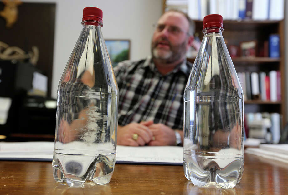 David Harris, the city of Brownwood's utilities director, shows bottles of treated sewage (left) and regular tap water. Photo: Jerry Lara, San Antonio Express-News / ©2013 San Antonio Express-News