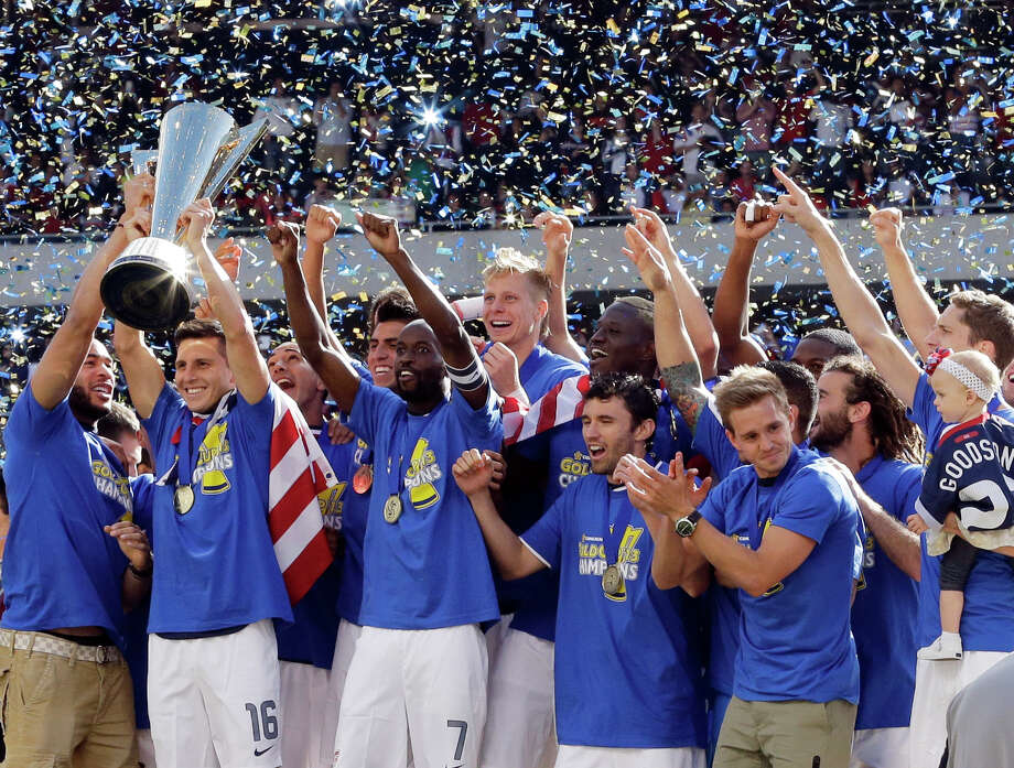 United States' Jose Torres (16), left, holds the trophy as he celebrates with teammates after defeating Panama 1-0 during the CONCACAF Gold Cup final soccer match at Soldier Field, Sunday, July 28, 2013, in Chicago. (AP Photo/Nam Y. Huh) Photo: Nam Y. Huh, Associated Press / AP