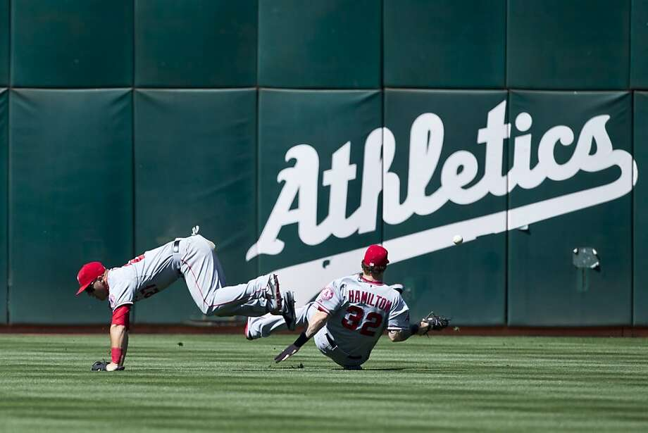 Mike Trout (left) and Josh Hamilton collide on what became a double for Stephen Vogt to ignite the A's five-run sixth inning. Photo: Jason O. Watson, Getty Images