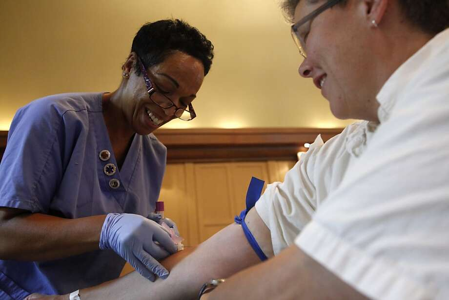 EMT Juveda Faciane extracts blood from Polly Pagenhart of Berkeley, so she can participate in the Cancer Prevention Study-3. Photo: Katie Meek, The Chronicle