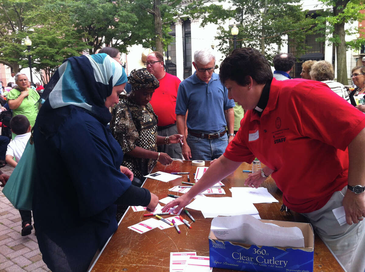 Rev. Sara Smith, of the United Congregational Church, gives Bridgeport resident Rita Hassan a name tag for an interfaith event about the Muslim observance of Ramadan in downtown Bridgeport on Sunday, July 28, 2013.