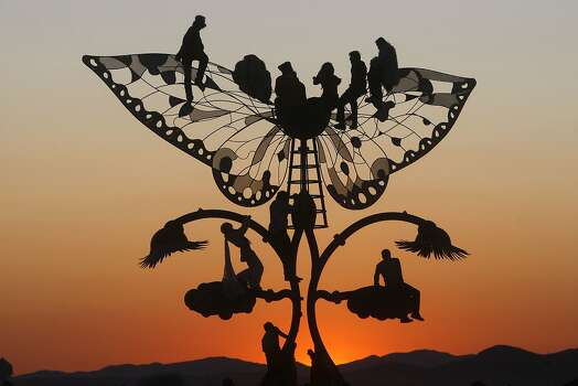 Burners climb a butterfly sculpture to watch the sun rise over the expanse of the Black Rock Desert known as the Playa. Photo: Frederic Larson, The Chronicle
