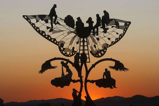 Burning Man festival participants climb a huge butterfly art structure to watch the sunrise over the playa on September 5, 2009 in Black Rock City, N.V. Photo: Frederic Larson, The Chronicle