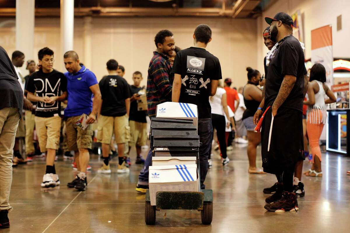 Carlos Sanchez of Missouri City talks with fellow sneaker heads as he carries around his personal collection on a dolly, during the 2013 H-Town Sneaker Summit.