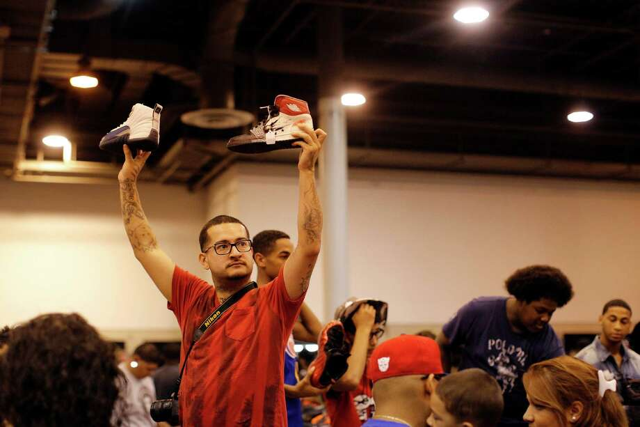 Jose Ramos holds up two different pair of Nike Air Jordan's in an attempt to find a buyer. Photo: © TODD SPOTH PHOTOGRAPHY, LLC / © TODD SPOTH PHOTOGRAPHY, LLC