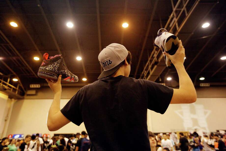 15-year-old Daniel Hardy of Houston holds up shoes in an attempt to find a buyer during the 2013 H-Town Sneaker Summit at Reliant Center in Houston, Texas. Photo: © TODD SPOTH PHOTOGRAPHY, LLC / © TODD SPOTH PHOTOGRAPHY, LLC
